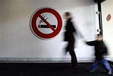 """<p>A woman walks past a """"No Smoking"""" sign in Nice, southeastern France, February 12, 2007. REUTERS/Eric Gaillard</p>"""