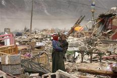 <p>Женщина с ребенком стоит на развалинах домов, разрушенных землетрясением в провинции Цинхай 19 апреля 2010 года. Почти 3.000 человек погибли или считаются пропавшими без вести в результате сильного землетрясения на северо-западе Китая в прошлом месяце, сообщило информационное агентство Синьхуа в понедельник. REUTERS/Donald Chan</p>