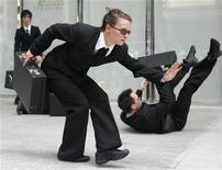 """<p>Performers wearing business suits act during a performance of """"The Agency"""" in Singapore's financial district May 21, 2009. REUTERS/Allison Ching</p>"""