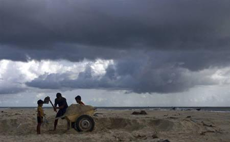 A man collects sand from a beach, against the backdrop of monsoon clouds on the outskirts of Kochi June 1, 2010. REUTERS/Sivaram V.