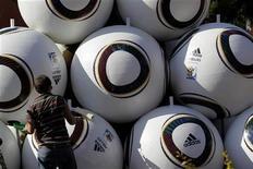 <p>Рабочий раскрашивает скульптуру из гигантских мячей в Йоханнесбурге 7 июня 2010 года. REUTERS/Ivan Alvarado</p>