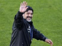 """<p>Técnico da seleção argentina, Diego Maradona, acena aos torcedores durante sessão de treino em Pretória. A Argentina sofreu para se classificar para a Copa do Mundo, mas a equipe do ex-craque vem emergindo um time menos defensivo e mais """"matador"""" do que a equipe que bateu a Alemanha num amistoso em março. 06/06/2010 REUTERS/Enrique Marcarian</p>"""