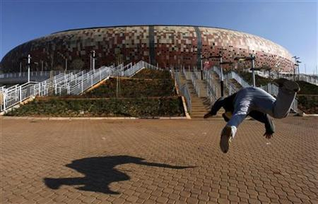 A sports enthusiast performs martial arts outside the Soccer City stadium in Soweto, Johannesburg, June 9, 2010. REUTERS/Thomas Mukoya