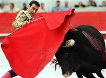 <p>Spanish bullfighter Enrique Ponce toys with a bull during Nimes feria, May 17, 1997. REUTERS/Stringer</p>