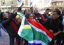 <p>Фанаты сборной ЮАР по футболу танцуют в центре Кейптауна 9 июня 2010 года. Хотя английский и является одним из официальных языков Южно-Африканской Республики, многим любителям футбола придется нелегко в повседневном общении из-за того, что местное население общается на дикой смеси африкаанс, зулу и девяти других языков страны. REUTERS/Yves Herman</p>