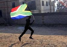 <p>A worker runs with the South African flag inside the Soccer City stadium in Soweto, Johannesburg June 10, 2010. REUTERS/Thomas Mukoya</p>
