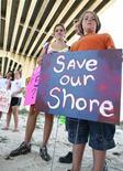 <p>Eli Torres de Orange Beach, Alabama (derecha) sostiene un letrero en una manifestación contra BP junto a su madre Tonya Torres bajo el puente Perdido Pass en Orange Beach, Alabama, jun 12 2010. REUTERS/ Lyle W. Ratliff (UNITED STATES)</p>