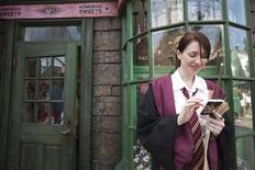 <p>A guest, in her Hogwarts school regalia, uses a mobile phone during the grand opening for The Wizarding World of Harry Potter at the Universal Studio Resort in Orlando, June 18, 2010. REUTERS/Scott Audette</p>