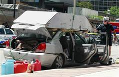 <p>Police inspect the vehicle of a 53-year-old man arrested after he allegedly tried to drive his car containing weapons and possible dangerous material close to the G20 summit area in downtown Toronto, June 24, 2010. REUTERS/Christinne Muschi</p>