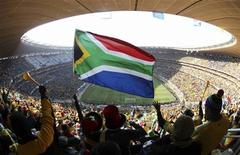 <p>Fans hold up a South African flag before the 2010 World Cup opening match between South Africa and Mexico at Soccer City stadium in Johannesburg June 11, 2010. REUTERS/Kim Kyung-Hoon</p>