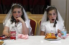 <p>Twin sisters Aine (L) and Emer Quinn eat sweets in the local parish hall after making their First Holy Communion in St Mary's Roman Catholic Church, Cushendall in this photo taken June 5, 2010. REUTERS/Cathal McNaughton</p>