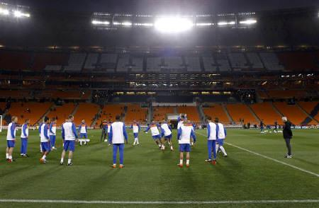 Netherlands' coach Bert van Marwijk (R) watches his players during a training session at Soccer City stadium in Johannesburg July 10, 2010, a day before they play Spain in the 2010 World Cup final.        REUTERS/Michael Kooren