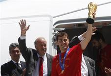 <p>Spain's captain Iker Casillas (R) next to Spain's coach Vicente del Bosque lifts the World Cup trophy after arriving at Madrid's Barajas airport July 12, 2010. Spain stunned the Netherlands to win their first World Cup on Sunday in sensational fashion with a goal in the last minutes of extra time. REUTERS/Gustau Nacarino</p>
