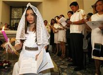 <p>Singer Charice Pempengco holds a candle during her baptism and confirmation at a Cathedral in Pasig City Metro Manila May 22, 2010. REUTERS/ Cheryl Ravelo</p>