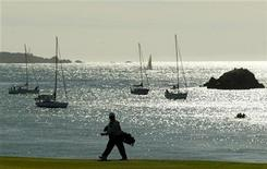 <p>Sailboats rest at anchor in Stillwater Cove as a caddy makes his way along the fourth fairway at Pebble Beach Golf Links in Pebble Beach, California February 8, 2004. REUTERS/Robert Galbraith</p>