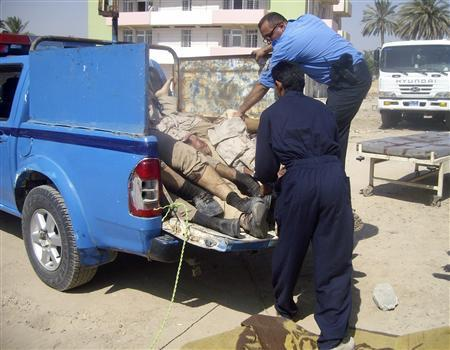 A policeman and a worker unload the bodies of government-backed Sunni militia members who were killed in a bomb attack, at a hospital in the town of Mahmudiya, 30 km (20 miles) south of Baghdad July 18, 2010. REUTERS/Stringer