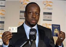 """<p>Wyclef Jean, nascido no Haiti, segura """"Green Card"""" dos EUA e passaporte haitiano depois de visitar o Haiti após o terremoto, em coletiva de imprensa em janeiro. O premiado cantor anunciou na quinta-feira que tomou providências legais para eventualmente se candidatar a presidente do Haiti, mas que a decisão definitiva ainda não foi tomada. 19/01/2010 REUTERS/Ray Stubblebine</p>"""