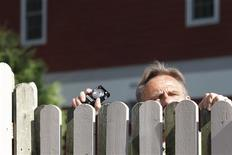 <p>A spectator peeks over a fence as he tries to look at guests departing for Chelsea Clinton's wedding in Rhinebeck, New York July 31, 2010. REUTERS/Jessica Rinaldi</p>