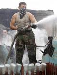 <p>Пожарный тушит огонь около города Воронежа, 30 июля 2010 года. Российские чиновники мобилизовали силы на борьбу с лесными пожарами после того, как больше 1000 семей остались без крова и по меньшей мере 34 человека погибли в огне, и отчитались о масштабных тратах на ликвидацию последствий стихии. REUTERS/Sergei Karpukhin (RUSSIA - Tags: ENVIRONMENT DISASTER)</p>