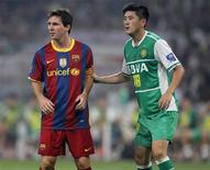 <p>Lionel Messi do Barcelona(esq) ao lado de Lu Jiang do Beijing Guoan em amistoso em Pequim. O time reserva do Barcelona, reforçado com participações rápidas de Lionel Messi e Zlatan Ibrahimovic, venceram a partida por 3 x 0. 08/08/2010 REUTERS/Petar Kujundzic</p>