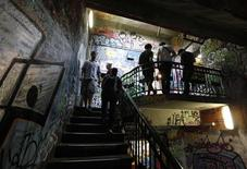 <p>People stand in the graffiti-covered staircase of the Tacheles alternative art centre in Berlin, August 7, 2010. REUTERS/Thomas Peter</p>
