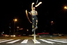 <p>Fabiano Cordeiro juggles flaming torches on a road crossing in Sao Paulo July 30, 2010. REUTERS/Nacho Doce</p>