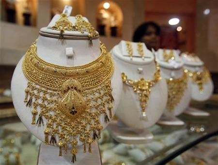 A saleswoman stands behind the showcased gold necklaces at a jewellery showroom in Agartala, capital of India's northeastern state of Tripura, August 18, 2010. REUTERS/Jayanta Dey
