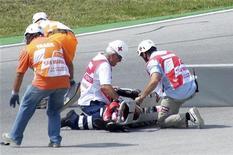 """<p>Врачи пытаются оказать помощь попавшему в аварию японскому мотогонщику в классе Moto2 Сёи Томидзаве на трассе в Сан-Марино 5 сентября 2010 года. Девятнадцатилетний японский мотогонщик в классе Moto2 Сёя Томидзава скончался после серьезной аварии на """"Гран-при Сан-Марино"""" в воскресенье, став уже второй жертвой скоростного вида спорта на последних двух соревнованиях, сообщил один из обслуживающих гонку врачей Клаудио Коста. REUTERS/Stringer</p>"""