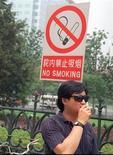 """<p>Мужчина курит под знаком """"Не курить"""" в Пекине 18 июня 1997 года. Самый жесткий запрет на курение в Китае, подразумевающий штрафы в $7, будет введен в Гуанчжоу для того, чтобы люди меньше """"смолили"""" во время ноябрьских Азиатских игр, сообщило государственное информационное агентство в среду.</p>"""