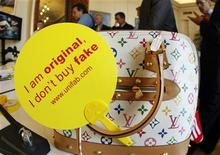 <p>A campaign slogan, 'I am original, I don't buy fake' is displayed on a counterfeit Louis Vuitton luxury handbag by French Customs officers before a destruction operation in Cannes, southeastern France September 28, 2009. REUTERS/Eric Gaillard</p>