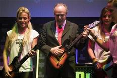 <p>French Culture Minister Frederic Mitterrand (C) plays Guitar Hero 5 game during the video game show in Paris September 17, 2009. REUTERS/Charles Platiau</p>