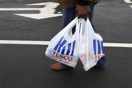A man carries a carrier bag as he leaves a Tesco supermarket in Hendon in London January 12, 2010. REUTERS/Stefan Wermuth