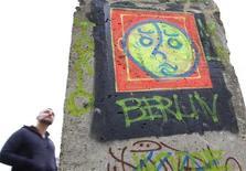 """<p>Мужчина стоит перед фрагментом Берлинской стены в Брюсселе, 9 ноября 2009 года. Студент из Германии создал компьютерную """"стрелялку"""", где игроки смогут примерить на себя роль пограничников ГДР, расстреливая политических беженцев, чем вызвал возмущение родственников жертв коммунистического режима. REUTERS/Yves Herman</p>"""