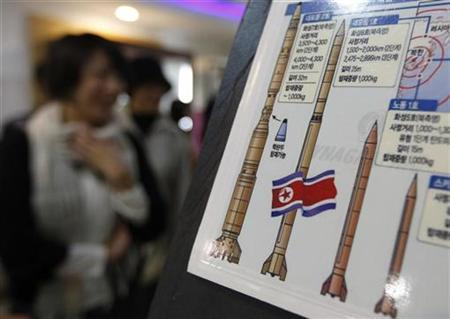 Japanese tourists walk past a display showing North Korea's missile system at a South Korean observation post near the demilitarised zone separating the two Koreas in Paju, about 45 km (28 miles) north of Seoul in this October 13, 2009 file photo. REUTERS/Lee Jae-Won
