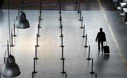 <p>A passengers walks past empty counters in a file photo. REUTERS/Eric Gaillard</p>