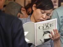 """<p>A woman reads a brochure for the movie """"The Cove"""" at a theatre in Tokyo July 3, 2010. REUTERS/Issei Kato</p>"""