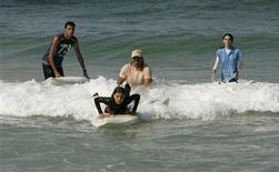 <p>Rajab Abu Ghanim (rear C) teaches his daughter, Palestinian girl Shorouq Abu Ghanem, to surf in the Mediterranean Sea off the coast of Gaza City November 5, 2010. REUTERS/Ismail Zaydah</p>