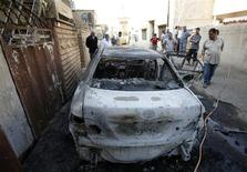 <p>Residents look at a damaged vehicle after a bomb attack in Baghdad November 10, 2010. REUTERS/Saad Shalash</p>