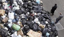 <p>Pedestrians walk past a pile of garbage in downtown Naples, November 19, 2010. REUTERS/Ciro De Luca</p>