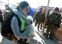<p>Animal rights activist Park So-youn holds stray dogs rescued from a village damaged by North Korean artillery shelling, as South Korean marines stand nearby, on Yeonpyeong Island November 29, 2010. South Korean President Lee Myung-bak labelled North Korea's artillery attack on a southern island a crime against humanity and said Pyongyang will pay the price for any further provocation. North Korea fired shells at the island off the peninsula's west coast on Tuesday, killing two civilians and two soldiers and destroying dozens of houses. REUTERS/Jo Yong-Hak</p>