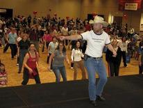 """<p>Adam Herbel, a.k.a. the Dancing Cowboy, leads a line dancing session at Santa Clara Convention Center, Santa Clara, California, in this 2010 handout photo. Herbel teaches country line dancing at The Rodeo Club in San Jose, California. He said some come for the exercise, some for the music and atmosphere. Though deeply rooted in Irish and German folk traditions, line dancing was off most urban grids until 1992 when Billy Ray Cyrus, father of teen idol Miley, stomped upon the stage with his megahit """"Achy Breaky Heart."""" Today line dancing is a worldwide phenomenon. Devotees have formed organizations as far away as Singapore and Australia. REUTERS/El Camino Day of Dance/Handout</p>"""
