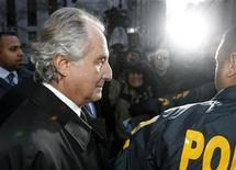 <p>Disgraced financier Bernard Madoff is escorted by police and photographed by the media as he departs U.S. Federal Court after a hearing in New York, January 5, 2009. REUTERS/Lucas Jackson</p>