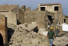 <p>Workers stand by debris after a house, once used by gladiators to train before combat, collapsed in Pompeii November 6, 2010. REUTERS/Ciro De Luca</p>