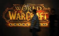 <p>A visitor walks past a placard of 'World of Warcraft' at their exhibition stand at the Gamescom 2010 fair in Cologne in this August 18, 2010 file photo. REUTERS/Ina Fassbender</p>