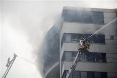<p>Пожарные борются с огнем на фабрике в Ашулии 14 декабря 2010 года. Около 20 человек погибли и более 100 пострадали в результате пожара на многоэтажной швейной фабрике в 25 километрах от столицы Бангладеш Дакки, сообщили местные телеканалы. REUTERS/Andrew Biraj</p>