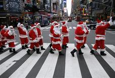 """<p>Люди, переодетые в Санта-Клаусов, маршируют по Нью-Йорку 27 ноября 2009 года. Необычного Санта-Клауса с мешком банкнот по $100 и в окружении полиции и """"эльфов"""" засекли недавно в бедных кварталах Канзас-Сити, когда он раздавал деньги страждущим. REUTERS/Brendan McDermid</p>"""
