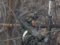 <p>Южнокорейский солдат патрулирует границу демилитаризованной зоны, разделяющей две Кореи, 20 декабря 2010 года. Южная Корея в понедельник начала учения с боевой стрельбой на острове в Желтом море в районе спорных территорий, несмотря на угрозу войны со стороны Пекина и просьбу России и Китая отменить тренировки. REUTERS/Jo Yong-Hak</p>