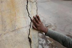 <p>Житель Карачи показывает трещину в стене своего дома, образовавшуюся в результате землетрясения, 19 января 2011 года. Сильное землетрясение магнитудой 7,2 балла произошло в юго-западной части Пакистана в среду. REUTERS/Athar Hussain</p>