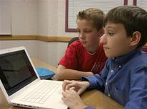 <p>Robert Nay, 14, the inventor of the world's most frequently downloaded free iPhone application, shows his friend William Graham (L) his Bubble Ball video game at a library in Spanish Fork, Utah, January 15, 2011. REUTERS/James Nelson</p>