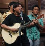 <p>Indonesian musician Bona Paputungan, wearing a similar centre-parted wig to the one used by corrupt tax official Gayus Tambunan, performs during a recording for a local TV station in Jakarta January 24, 2011. REUTERS/Crack Palinggi</p>